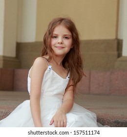 Little girls in white dresses with long hair outdoors