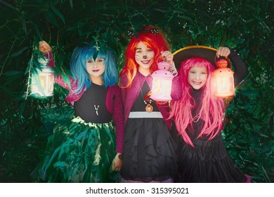 Little girls in wigs and Halloween costumes holding lanterns and looking at camera