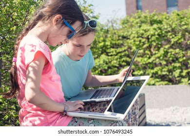 Little girls working with laptop in the park.