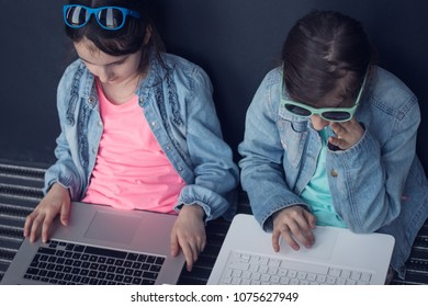 Little girls working together on laptop.