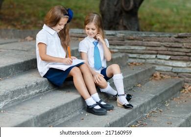 Little girls writting in exercise book in the park