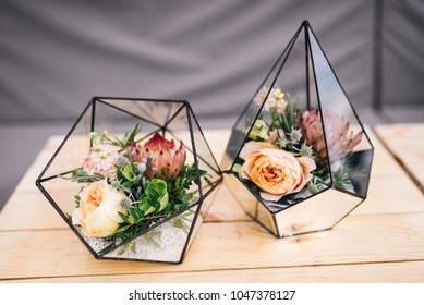 Little glass vases with fresh bouquet stands on the table. Roses in florariums, decor.