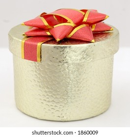 Little golden present box with big red bow on top.
