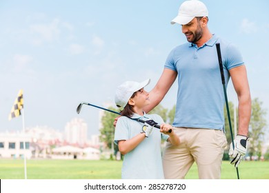 Little golfer with father. Happy young man and his son holding golf clubs and looking at each other while standing on the golf course