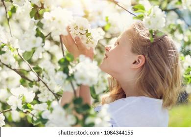 Little gorgeous girl in spring white flowers