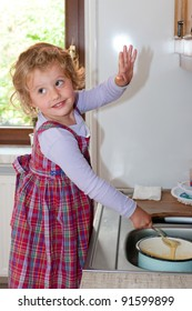 Little granddaughter helping grandma in a kitchen