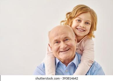 Little granddaughter hugging her grandfather