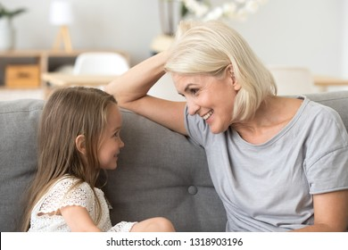 Little granddaughter talking with attentive happy grandmother, sitting on cozy sofa at home, smiling grandma with little girl having pleasant conversation, grandchild with granny having fun together
