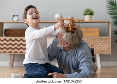 Little grandson playing together with 60s grandfather different generations age men have fun on warm floor boy holding helicopter wooden toy imagines himself dreams become a pilot in future concept