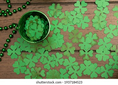 Little green cup full of clovers and clovers on wooden background. Saint Patrick's Day decoration