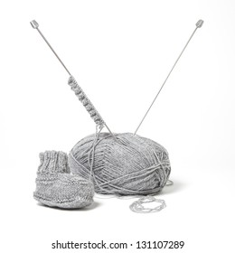 A little grey booty with a ball of wool and the needles. Square Format.