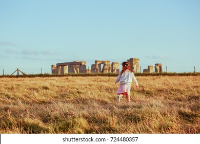 Little gril running near Stonehenge England travel destination vacation in South England, Europe