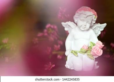 Little guardian angel holding flowers