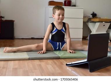Niñito de gimnasta dividido en entrenamiento en línea con laptop en casa