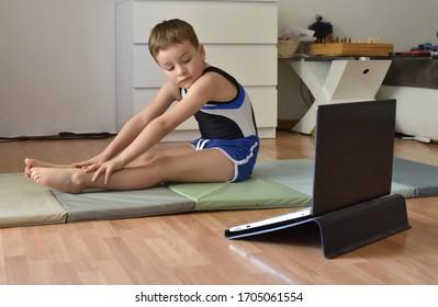 El niño pequeño gimnasta se está entrenando en línea con una laptop en casa