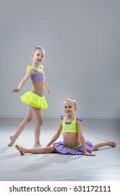 little gymnast girls in the studio gray background