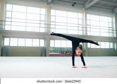 little gymnast standing on hand doing the splits