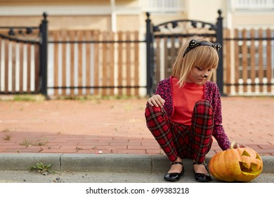 Little halloween girl with jack-o-lantern sitting on pavement not far from fence