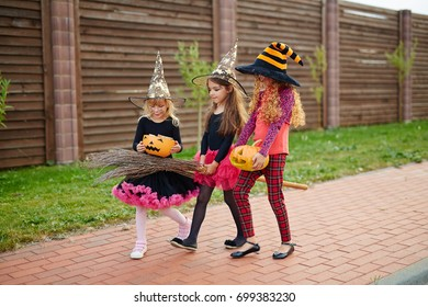 Little halloween witches in hats moving down pavement during trick-or-treat promenade
