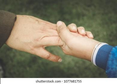 A little hand holdind a big hand, close up.