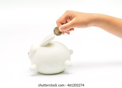 little hand inserting a coin in a white rabbit bank against a white background