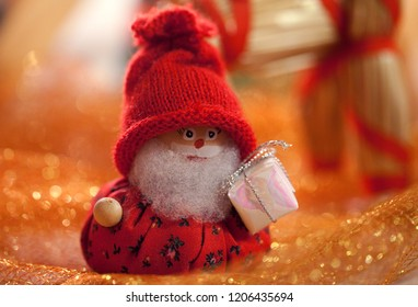 little handmade dwarf with red cap and parcel as christmas decoration surrounded by golden environment and background