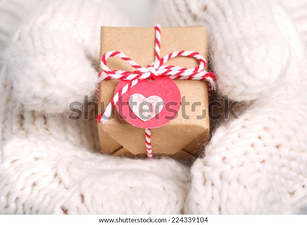 Little handmade gift box with heart tag in womans hands with white warm gloves