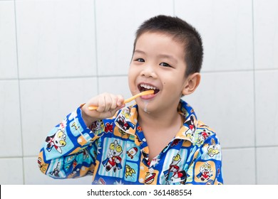 Little handsome Asian boy brushing Teeth in bath with smiling face