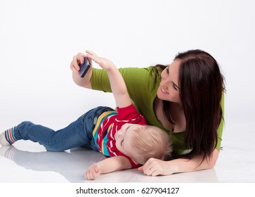 little handsome boy with mother playing with cell phone isolated on white