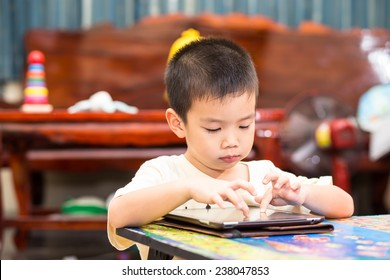 Little handsome boy touch on ipad tablet and playing game at home