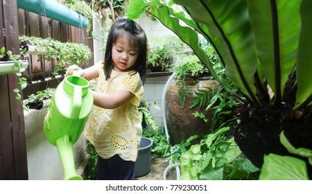 Little happy asian girl watering garden.