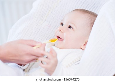 Little happy baby feeding with a spoon