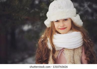little happy beautiful girl in winter forest