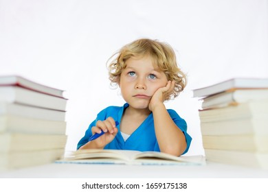 Little happy boy between 4 and 5 years old and thoughtful look sitting at a desk doing his homework, with textbooks on his table and with a white background
