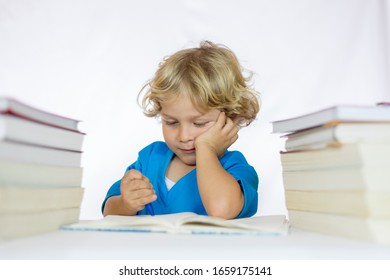 Little happy boy between 4 and 5 years old sitting at a desk doing his homework, with textbooks on his table and with a white background