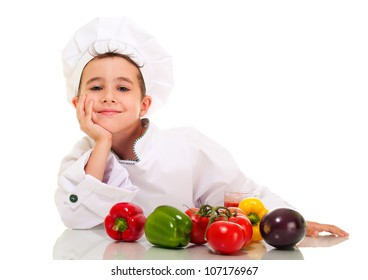Little happy boy chef in uniform with vegetables lean on hand isolated on white