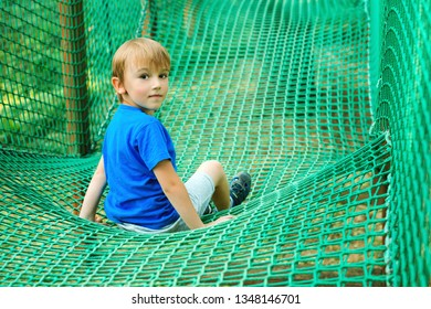 Little happy boy having fun in adventure park. Child playing at outdoors playground. Happy childhood. Summer holidays. Kid plays in rope adventure park. Obstacle course for children