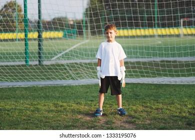 little happy boy on football field