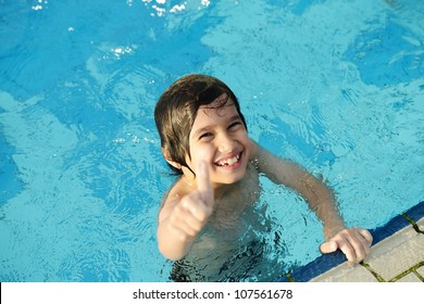 Little happy boy on pool with thumb up