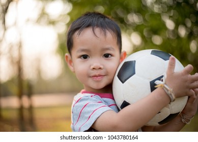 Little happy boy playing Soccer In Park