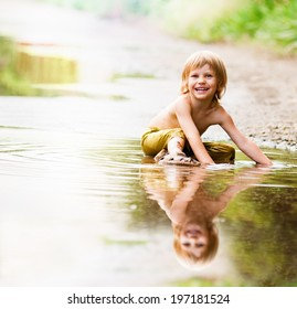 little happy boy in the puddle. summer outdoor