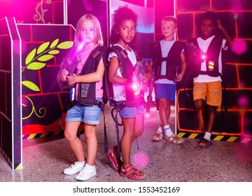 Little happy cheerful   african and european  girls standing back to back with laser pistols in dark lasertag room during game with friends