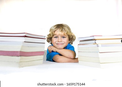 Little happy child between 4 and 5 years old sitting at a desk studying with textbooks on his table and with a white background