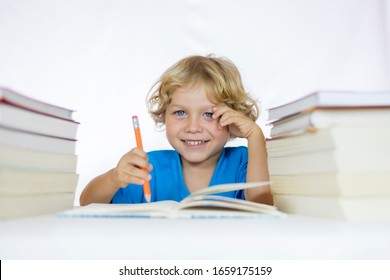 Little happy child between 4 and 5 years old sitting at a desk studying while holding a pencil with textbooks on his table and with a white background