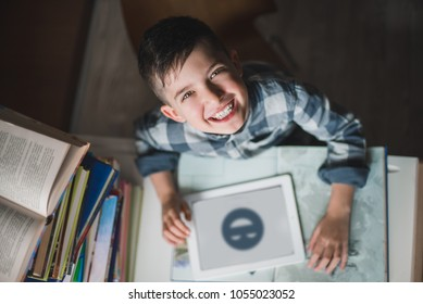 Little happy child boy is using a tablet and sitting at a table next to a pile of books.