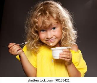 Little happy child eating yogurt