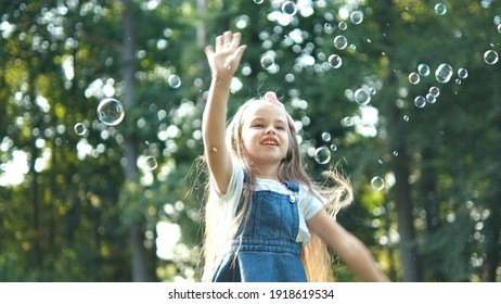 Little happy child girl cathing and bursting soap bubbles outdoors in summer.