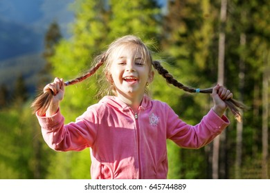 Little happy child with pigtails hair. The concept of childhood and lifestyle.