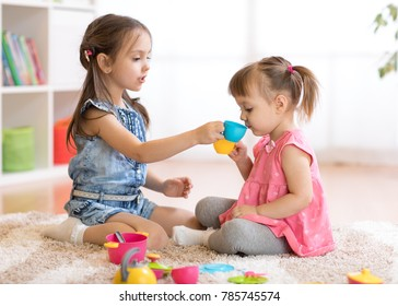 Little happy children, cute kids girls play with plastic toy kitchen on floor at home or kindergarten
