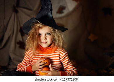 little happy cute shaggy with tangled hair witch 5 -6 years old laughing in black sorcerer hat portrait on dark bright background with pumpkin, halloween, sinister environment